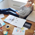 Relaxed confident female entrepreneur reclining back in her chair with her bare feet on the desk talking to a client on her mobile phone, high angle view on desk with paperwork, charts and laptop