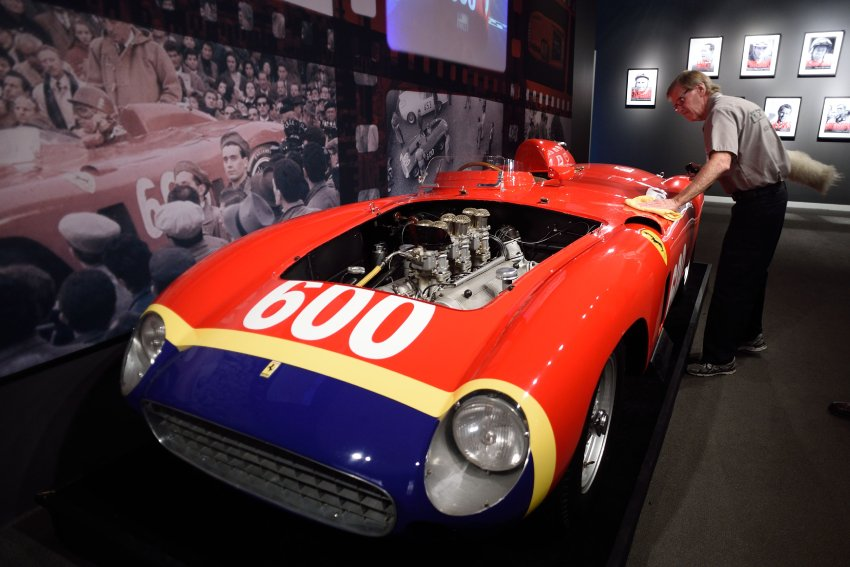 A Sotheby's employee dusts off the1956 Ferrari 290 MM by Scaglietti being exhibited at Sotheby's December 9, 2015 in New York. The car is to be auctioned December 10, 2015 during the Driven by Disruption auction at Sotheby's in New York. AFP PHOTO/DON EMMERT