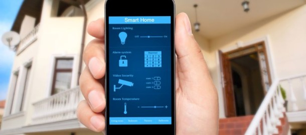 male hand hold a phone with system smart house on a screen on the background of the house