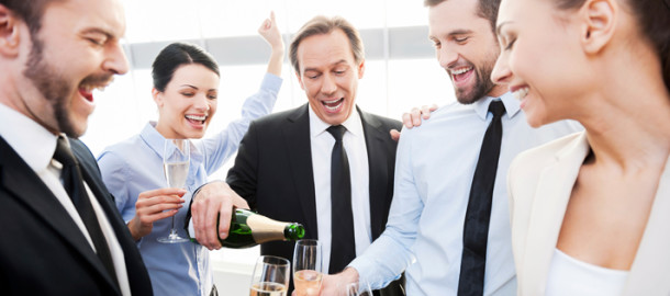 We absolutely deserve this! Group of happy business people holding flutes while mature man pouring champagne