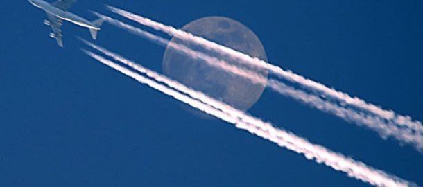 """ARCHIV - Ein Langstreckenflugzeug scheint am Mond vorbei zu fliegen und hinterlässt dabei Kondensstreifen am Himmel (Archivfoto vom 11.02.2006, aufgenommen in München). Kondensstreifen am blauen Himmel - bei vielen lösen sie Fernweh aus, Sehnsucht nach Urlaub und Sonne. Wissenschaftler dagegen sehen die weißen Streifen hinter Düsenjets zunehmend mit Sorge, denn sie beeinflussen unser Klima. In welchem Ausmaß sie schädlich wirken, darüber streiten die Forscher noch. Doch die Kondensstreifen sind nur ein sichtbares Zeichen des klimaschädlichen Luftverkehrs. Zudem beeinflussen freigesetztes Kohlendioxid und Stickoxide das Klima. Foto: Wolfgang Schneider dpa (zu dpa-Korr """"Forscher wollen Flugverkehr klimaschonender machen"""" am 24.05.2007) +++(c) dpa - Bildfunk+++"""