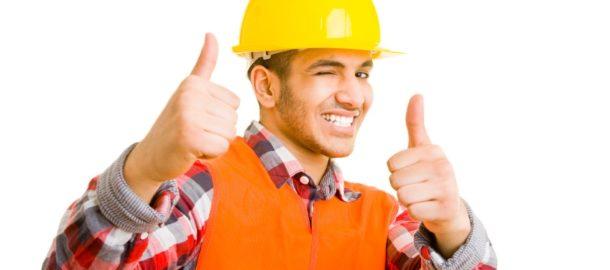 Bauarbeiter zwinkert und zweigt mit beiden Daumen nach oben