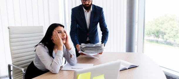 Businesswoman having headache for having too much work to get done from her boss