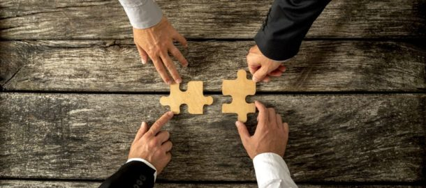 Four successful business men joining two puzzle pieces each being held by two partners, rustic wooden background. Conceptual of merger or creative cooperation of two business companies.