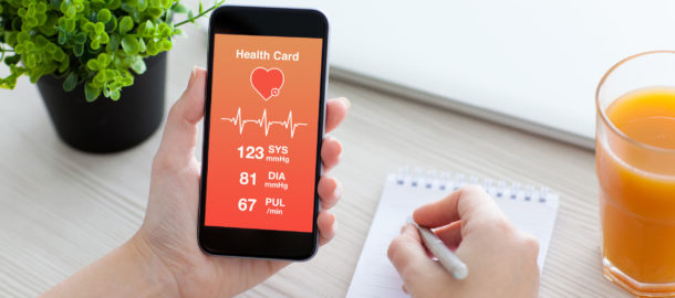38163261 - women hands holding phone with app for health card monitoring and writing in a notebook