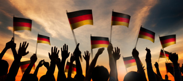 Silhouettes of People Holding the Flag of Germany