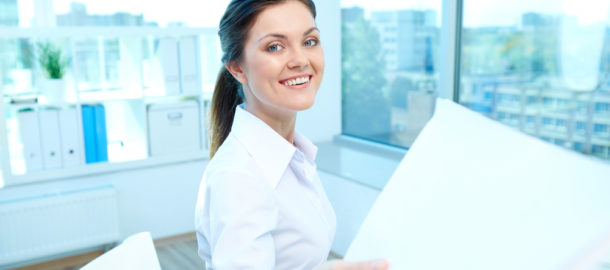 Portrait of young smiling female giving application to conductor