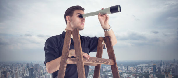 Young businessman looking for opportunities through the spyglass standing on the stairs.  Cloudy sky and city around.