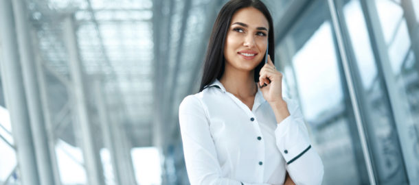 Business Woman Using Phone In Office. Portrait Of Beautiful Smiling Female In White Stylish Shirt Talking On Smartphone, Working In Office Environment. Phone Communication. High Resolution.